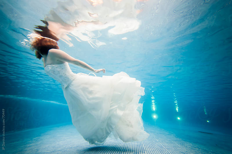 Trash the Dress Underwater Bride Swimming at the Surface by JP Danko for Stocksy United