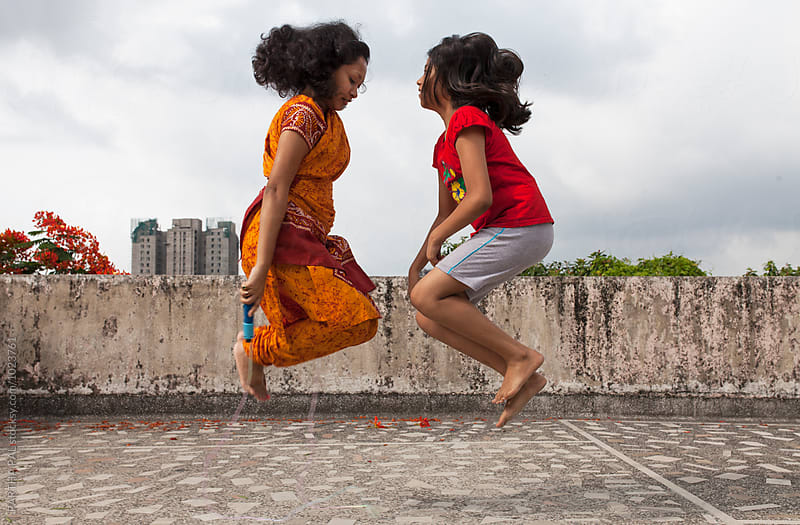 A woman and teenager jumping and playing together by PARTHA PAL for Stocksy United