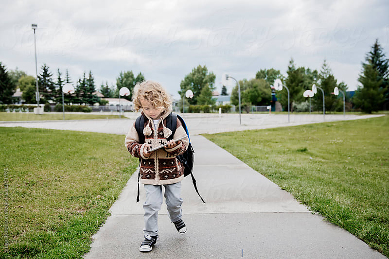 School boy walking and playing with a tablet by Shaun Robinson for Stocksy United