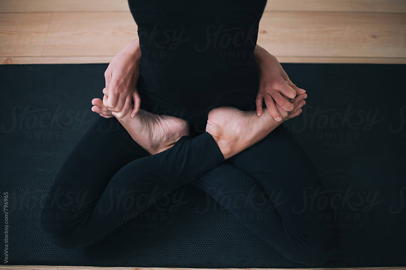 Woman practicing yoga indoor by Marija Mandic for Stocksy United