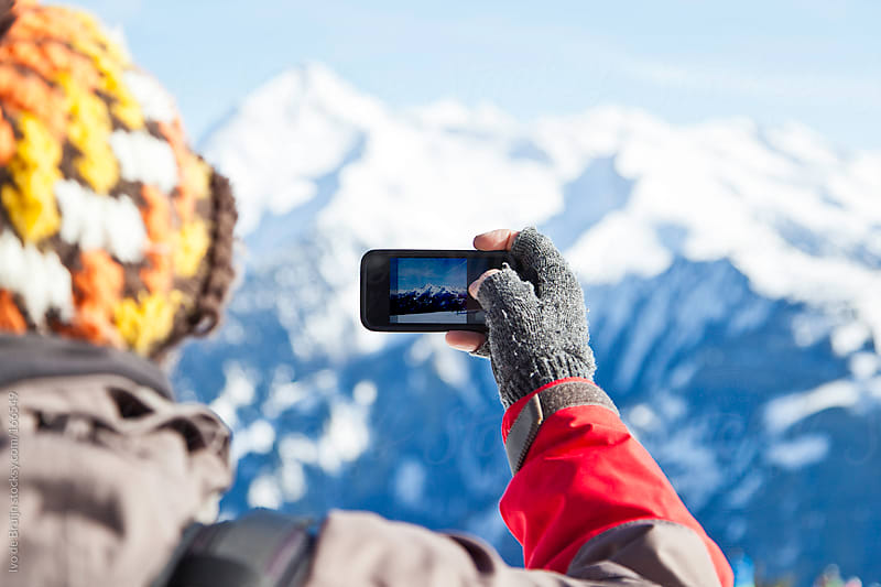 Man making a photo of mountain peaks with his phone by Ivo de Bruijn for Stocksy United