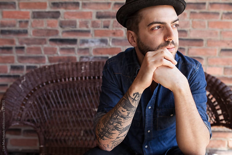 young brazillian tattooed man wearing fedora staring out window by Lisa MacIntosh for Stocksy United