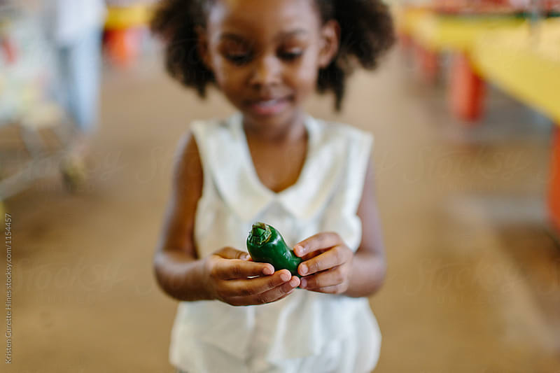 A little girl holding a green pepper by Kristen Curette Hines for Stocksy United