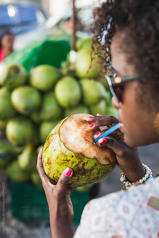 Brazilian Woman drinking coconut water by Mauro Grigollo for Stocksy United