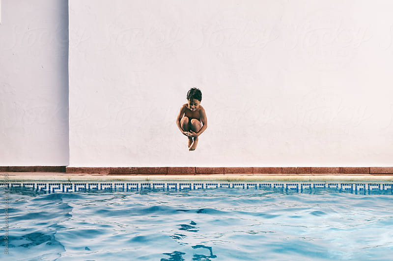 A little boy jumping into the swimming pool by Bisual Studio for Stocksy United