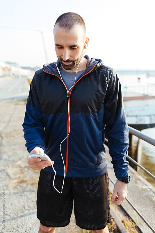 Runner Listening to Music on Mobile Phone by Lumina for Stocksy United