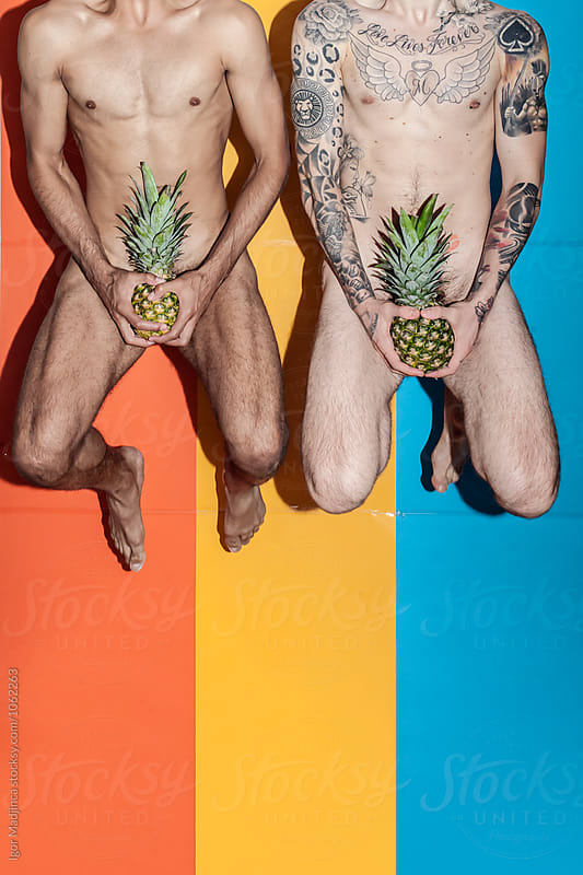 jump,two naked young man hiding with pineapple private parts in front of the colorful background, food,party,youth, crazy, summer by Igor Madjinca for Stocksy United
