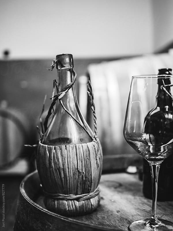 wicker wine bottle on a wooden barrel by Juri Pozzi for Stocksy United