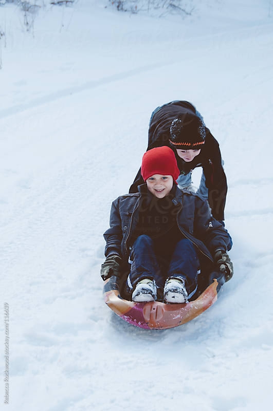 Sled riding in the snow by Rebecca Rockwood for Stocksy United