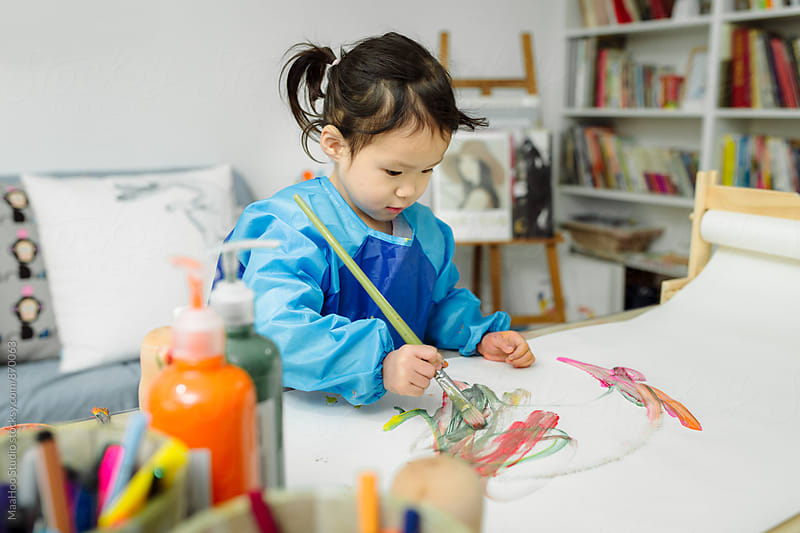 Little girl painting on paper by Maa Hoo for Stocksy United