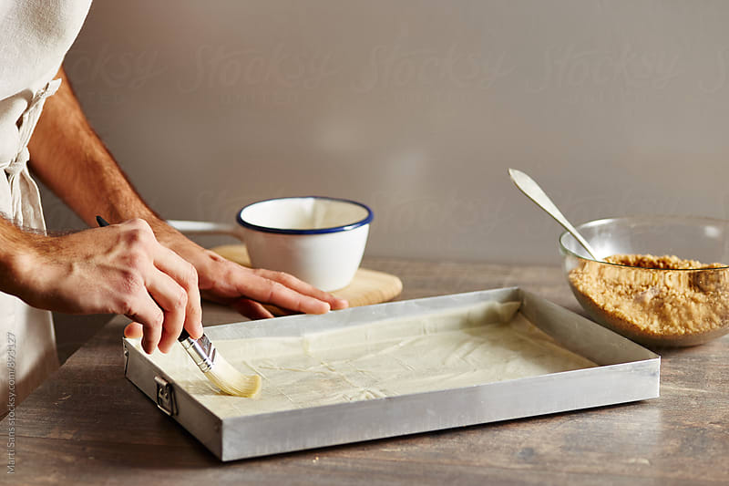 Chef's hands coats baking pan with melted butter by Martí Sans for Stocksy United