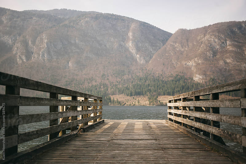 A platform at a lake with mountains in the background. by Koen Meershoek for Stocksy United