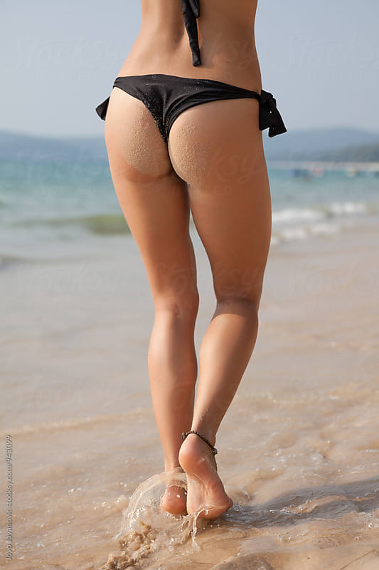 Woman walking at the beach wearing black bikini by Jovo Jovanovic for Stocksy United
