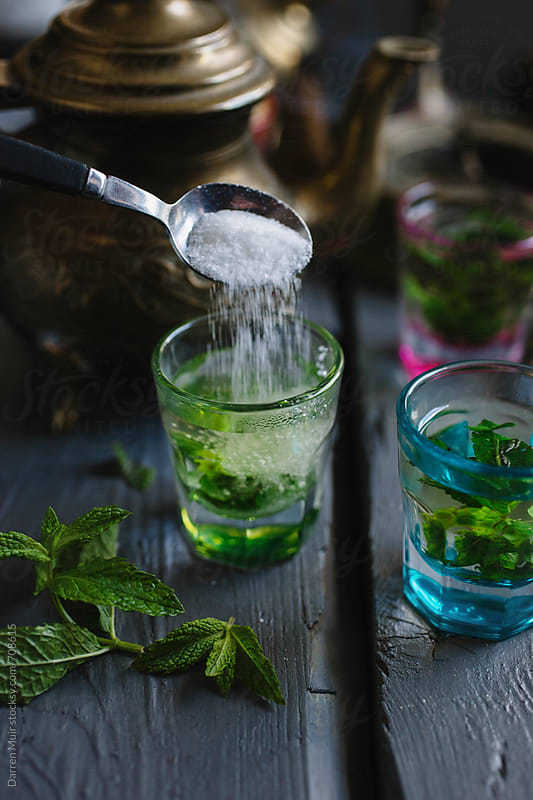 Pouring sugar into mint tea.  by Darren Muir for Stocksy United