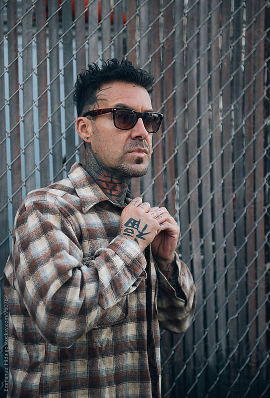 Tatted male buttoning up his flannel by Emmanuel Hidalgo for Stocksy United