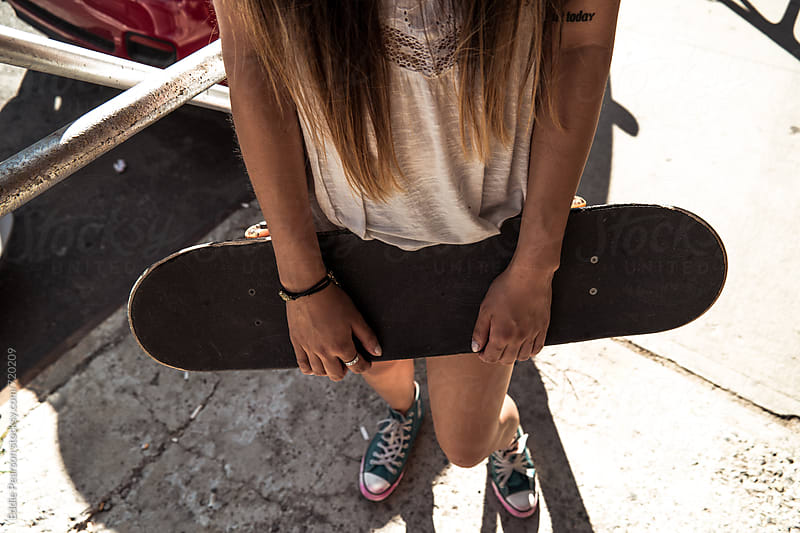 Closeup of a young woman holding a skateboard by Eddie Pearson for Stocksy United
