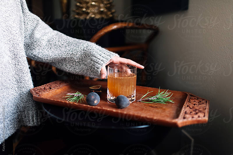Woman reaching for a cocktail by Kayla Snell for Stocksy United