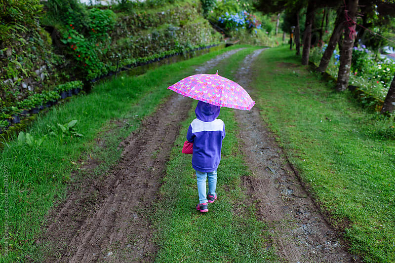 Child with umbrella walking on a mud road by Saptak Ganguly for Stocksy United