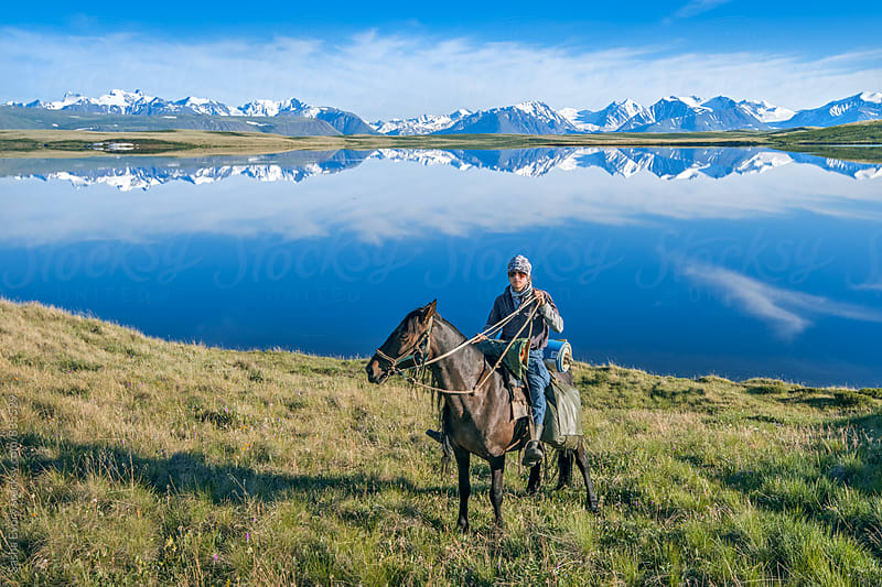 A man on the horse against mountain lake by Sasha Evory for Stocksy United
