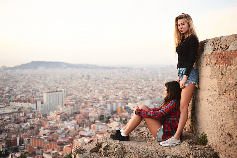 Two young women against of beautiful cityscape by Guille Faingold for Stocksy United
