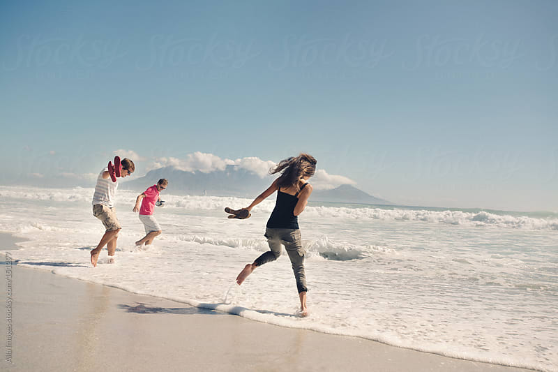 Friends jumping in the waves by Aila Images for Stocksy United