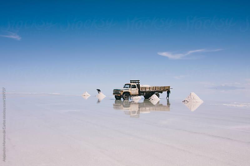 Car and workers on Uyuni salt flat, Bolivia travel image by Alejandro Moreno de Carlos for Stocksy United