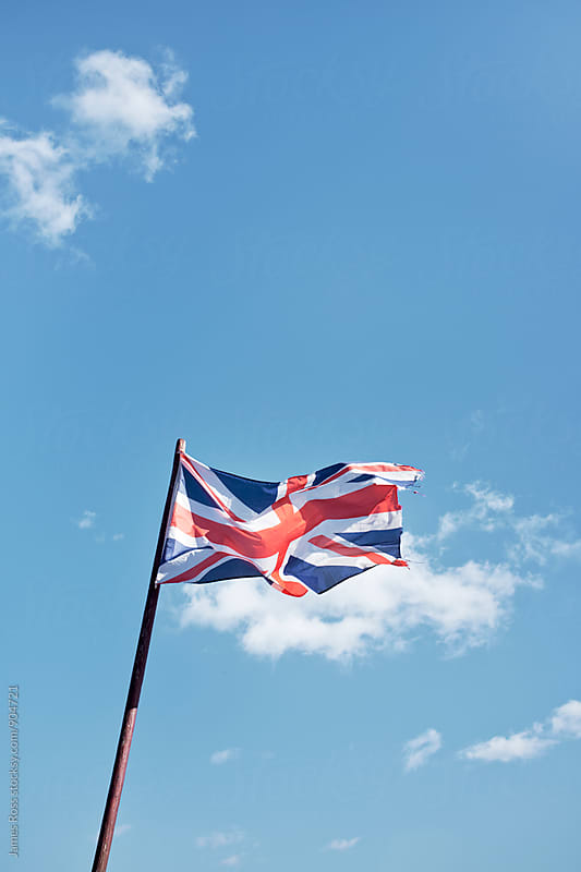 Union Jack flag against blue sky by James Ross for Stocksy United