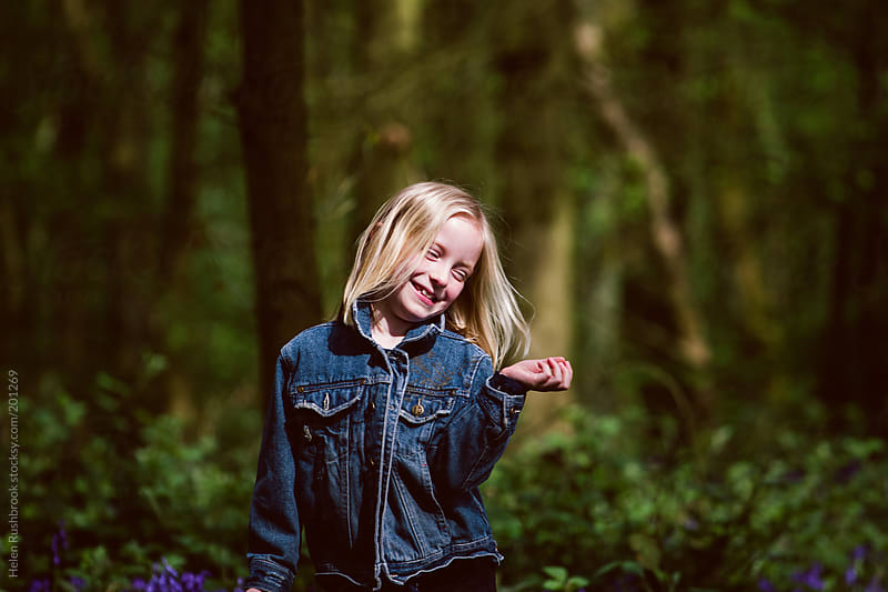 Smiling little girl in a forest by Helen Rushbrook for Stocksy United