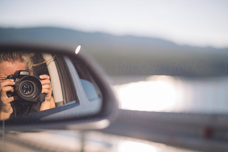 woman taking photos in the rear view mirror by RG&B Images for Stocksy United