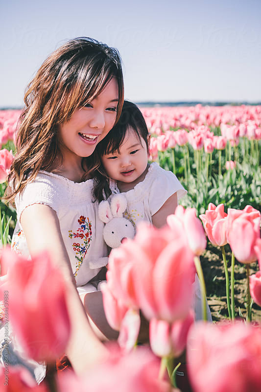 Happy Asian mother and daughter spending time together in a tulip field by Suprijono Suharjoto for Stocksy United