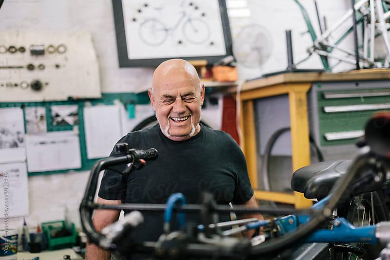 Smiling senior Bicycle Mechanic  by VegterFoto for Stocksy United