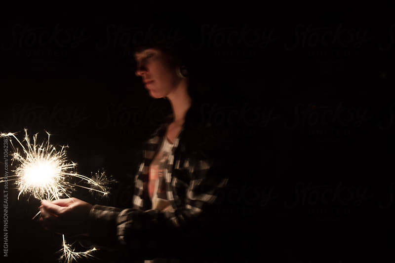 Young Woman at Night Illuminated by Sparklers by Meg Pinsonneault for Stocksy United