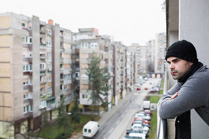 Young man standing on the balcony  by Jovana Rikalo for Stocksy United