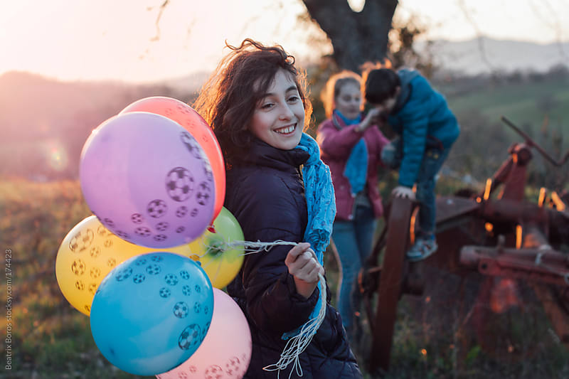 Girl holding ballons at Sunset in the countryside by Beatrix Boros for Stocksy United