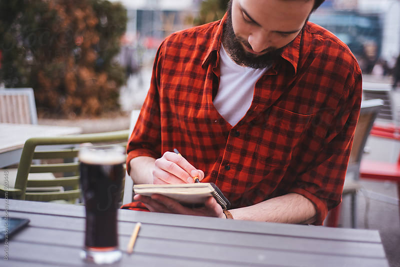 Bearded man drawing in coffee shop  by Boris Jovanovic for Stocksy United