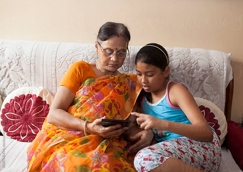 Grand mother learing to use Tablet from her Grand Children by PARTHA PAL for Stocksy United