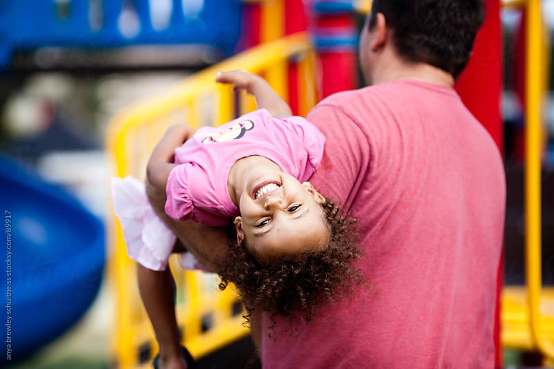 Portrait of young girl smiling happily as her father carries her away by anya brewley schultheiss for Stocksy United
