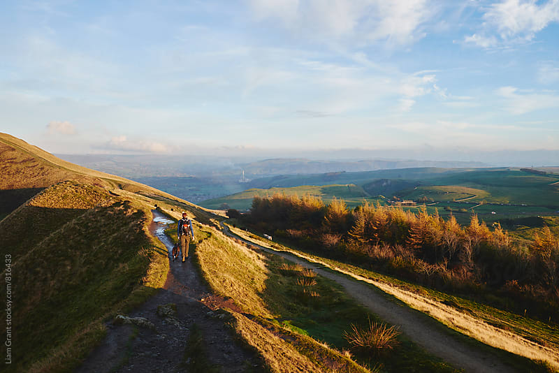 Male walking his dog on a mountain ridge at sunset. Derbyshire, UK. by Liam Grant for Stocksy United