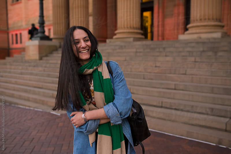 Woman smiling in front of steps by Reece McMillan for Stocksy United