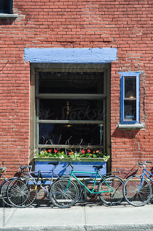 bikes chained up next to a brick wall on a sunny day by Amanda Large for Stocksy United