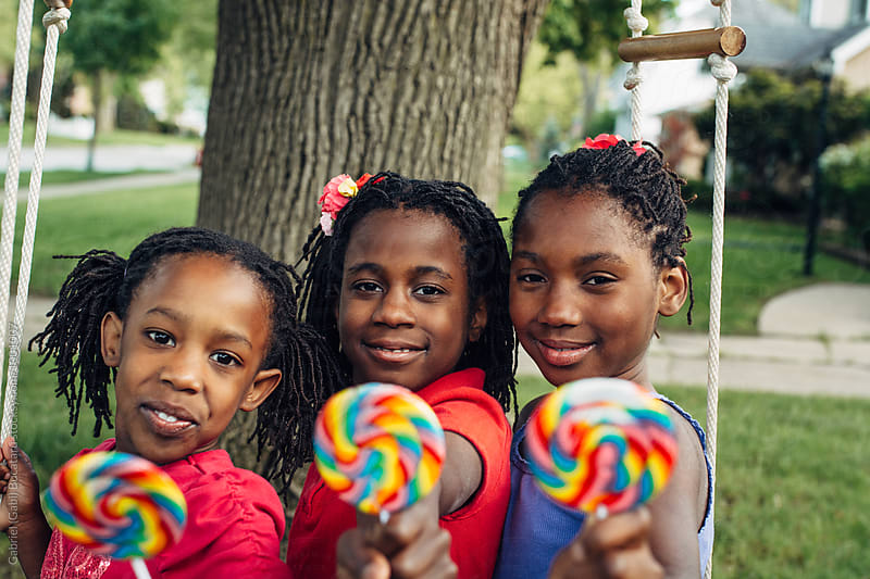 Three African American girls with lollipops on a swing by Gabriel (Gabi) Bucataru for Stocksy United