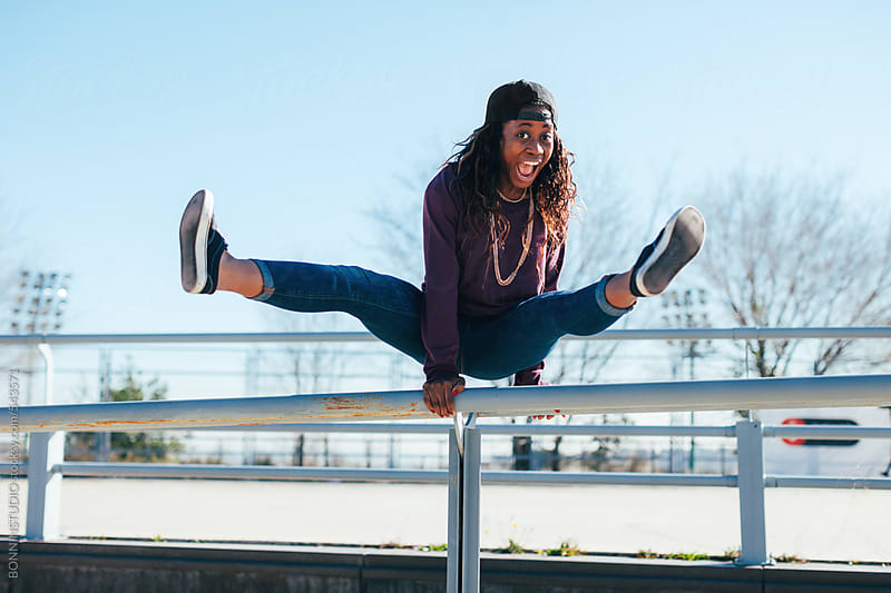 African american hip-hop style woman doing acrobatics on a fence in the city. by BONNINSTUDIO for Stocksy United