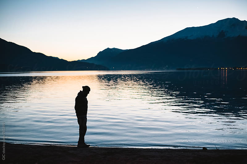 Man standing at twilight against lake by Simone Becchetti for Stocksy United
