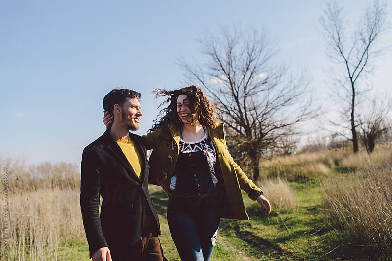 Young couple  laughing on the byway   by Evgenij Yulkin for Stocksy United