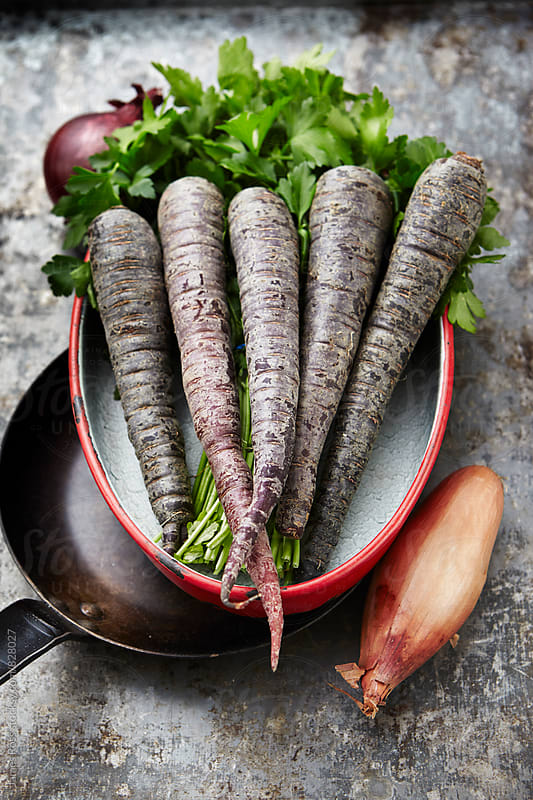 Purple carrots, onions and parsley in a pan by James Ross for Stocksy United