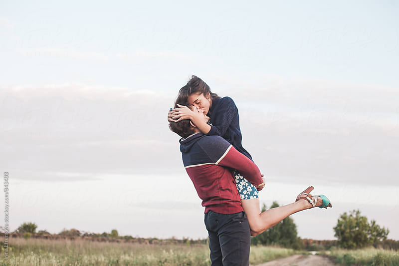 Young Man and Woman embracing in front of the sky by Irina Efremova for Stocksy United