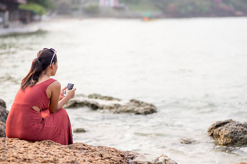 Asian girl in red dress using smart phone by the sea  by Soren Egeberg for Stocksy United