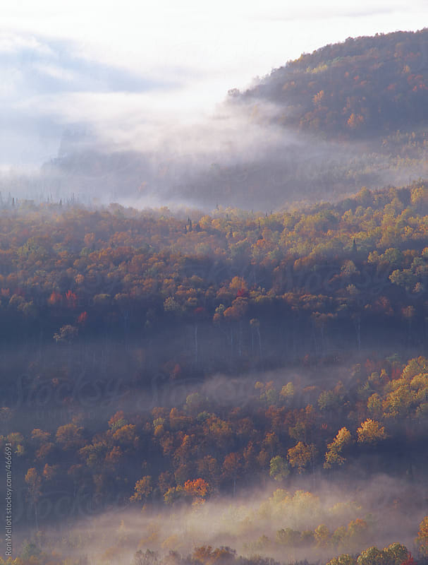 telephoto of sunrise painting a valley in upstate vermont in autumn color and fog mist by Ron Mellott for Stocksy United