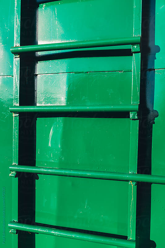 Ladder on green metal container, close up by Paul Edmondson for Stocksy United