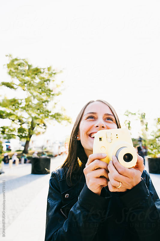 Smiling tourist woman taking a photo with her instant camera.  by BONNINSTUDIO for Stocksy United